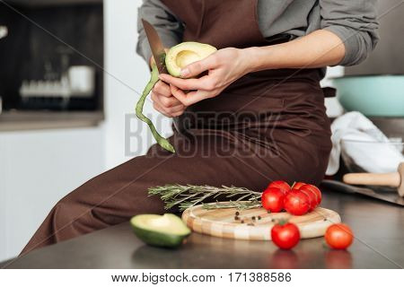 Cropped image of young woman standing in kitchen cut the tomatoes and avocado.