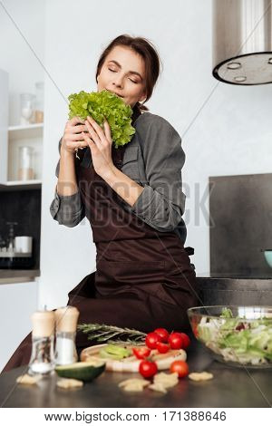 Photo of young woman standing in kitchen smells lettuce leaves and cooking with the tomatoes and avocado.