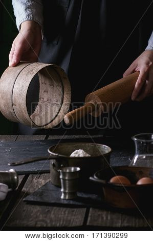 Female Hands With Wooden Rolling-pin And Sieve