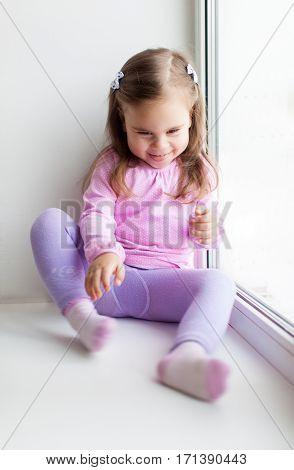 Cute little girl sitting on the windowsill near the window