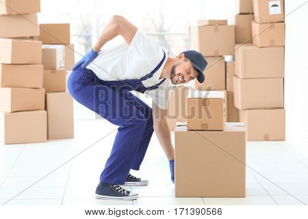 Man suffering from back ache while moving boxes indoors