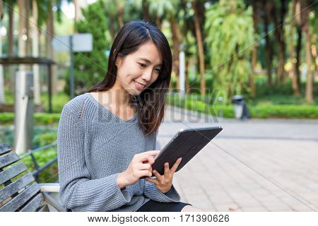 Woman use of digital tablet at park