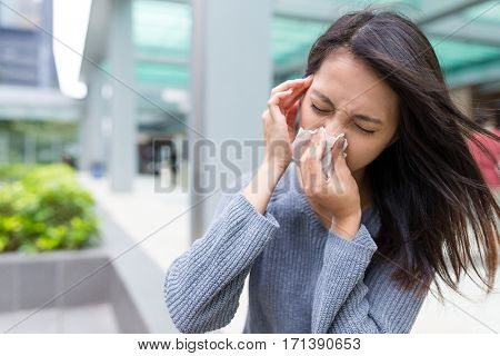 Woman feeling sick and sneezing on nose