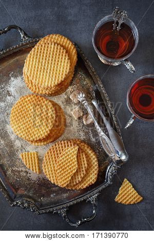 French waffles traditional norman biscuit on vintage tray and two cup tea. Dark photo top view
