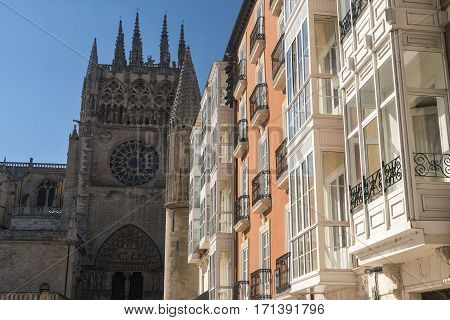 Burgos (Castilla y Leon Spain): exterior of the medieval cathedral in gothic style and houses with the typical verandas