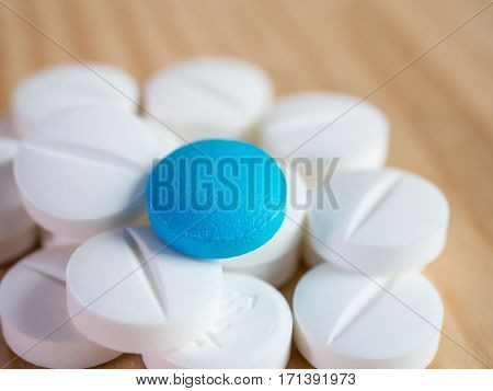 Closeup blue medicine pill over group of white medicine pill on wood background pharmaceutical theme (Selective focus)