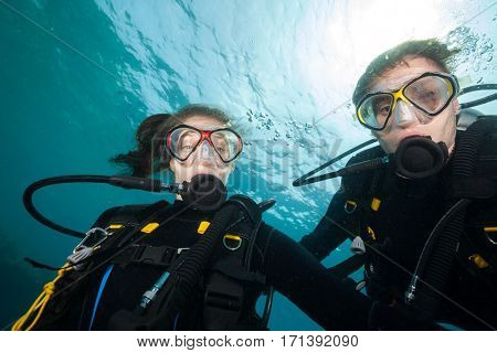 Couple of scuba divers looking at camera, selfie portrait