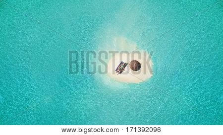 Young woman sunbathing on tiny sandy island with umbrella. Concept of summer beach vacation and travel.