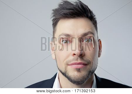 Portrait of workaholic or sleepless man with matches in eyes on light background. Concept of staying awake