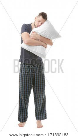 Young sleepy man in pajamas hugging pillow on white background