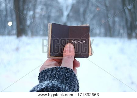 discover concept, traveler holds a book in his hand with the inscription on the background of the winter forest