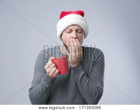 Sleepy guy in Xmas hat holding cup of coffee and yawning on light background
