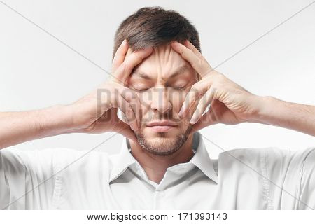 Young man with headache on white background