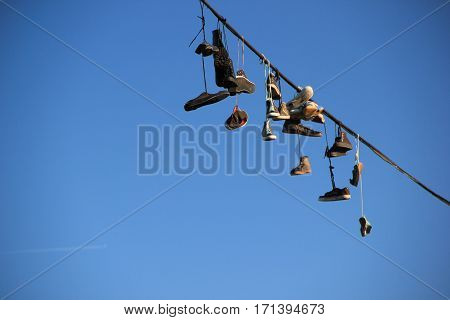 Shoes hanging on a rope with blue sky background
