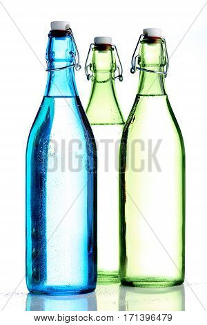 Colored bottles with caps on white background filled with water