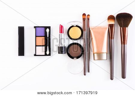 Makeup cosmetics, brushes and other essentials row on white background. Top view, flat lay. Multicolored beauty tools collection, lipstick, eyeshadow, mascara, foundation and more