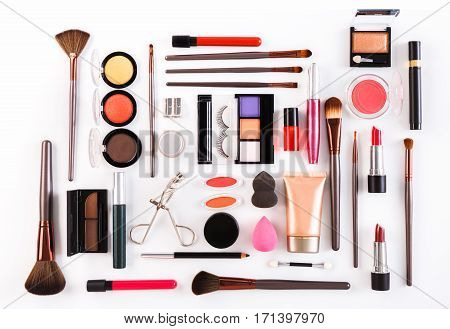 Makeup cosmetics, brushes and other essentials on white background. Top view, flat lay. Multicolored beauty tools and products collection, lipsticks, eyeshadow, mascara, sponge, eyelashes and more