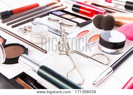 Makeup cosmetics, brushes and other essentials on white background. Flat lay. Multicolored beauty tools and products collection, lipsticks, eyeshadow, powder, mascara, sponge, eyelash curler
