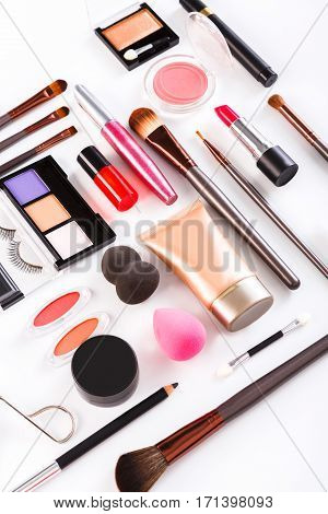 Makeup cosmetics, brushes and other essentials on white background. Flat lay, vertical. Multicolored beauty tools collection, foundation, lipstick, eyeshadow, pencil, sponge, eyelash curler