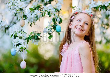 Adorable little girl playing with Easter eggs in a blooming garden on spring day