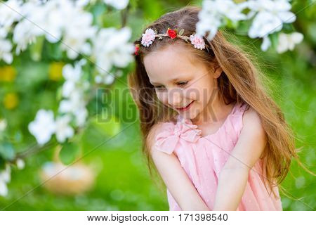 Adorable little girl in in blooming apple tree garden on spring day