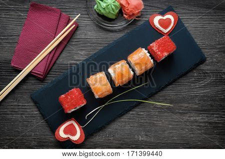 rolls of salmon, Philadelphia cheese, avocado with pickled ginger, wasabi, lying on a stone Board