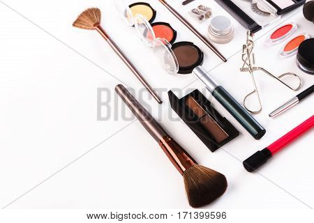Makeup cosmetics, brushes and other essentials on white background. Flat lay with copy space. Multicolored beauty tools and products collection, lipsticks, eyeshadow, eyelash curler