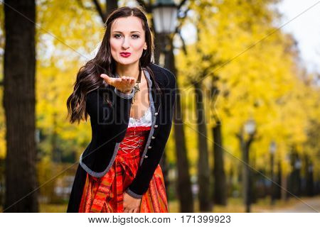 Bavarian Girl in Dirndl blowing a kiss, standing in front of an alley in fall