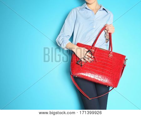 Fashion concept. Businesswoman holding red handbag on blue background, closeup