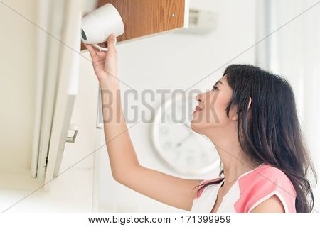 Asian woman putting cups in cupboard