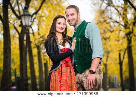 Man and woman wearing Bavarian Tracht, in close position, standing in front of an alley in fall