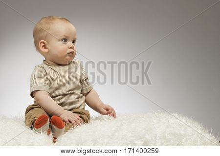 Adorable little baby sitting on the white blanket and looking away, studio shot, isolated on grey background. Lovely baby portrait