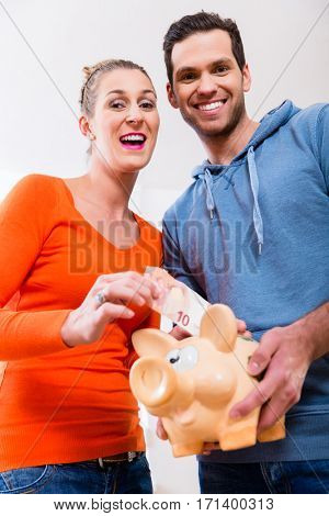 Couple saving money by moving house, piggybank standing on packing case