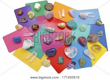 Combined Color Crystal Reading - color cards randomly scattered with a broad selection of healing crystals randomly scattered in preparation for a reading isolated on a white background