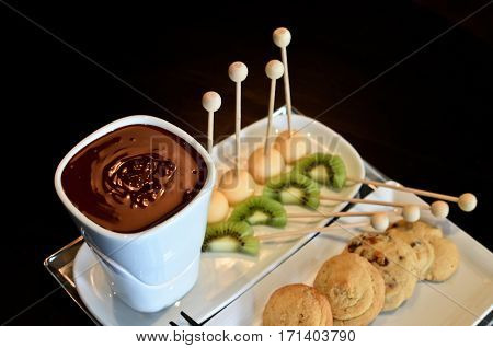 The chocolate fondue with a different fruits and cookies