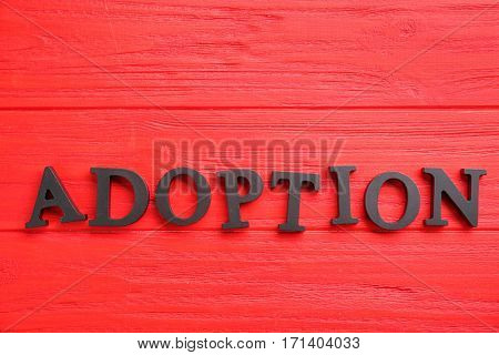Word ADOPTION on color wooden background