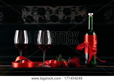 Wine bottle and two wineglasses decorated with red rose and ribbon on a dark background. Valentine's day theme concept