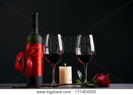 Wine bottle and two wineglasses with red rose and candle on a dark background. Valentine's day theme concept
