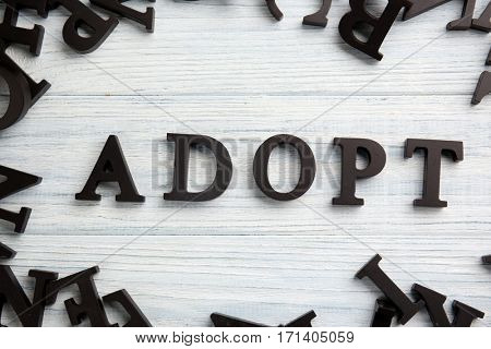 Word ADOPT on light wooden background