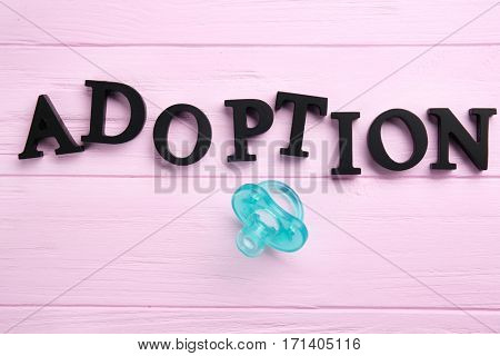 Word ADOPTION and passifier on color wooden background