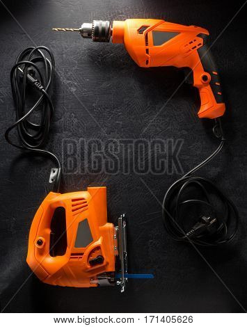 electric tools with cord on black background
