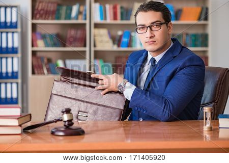 Handsome judge with gavel sitting in courtroom