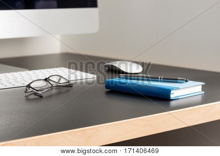 Gray Office Desk With Computer, Eyeglasses, A Pen And Notebook