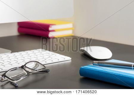 Notebook, Pen, And Eyeglasses Alongside Computer On Office Desk