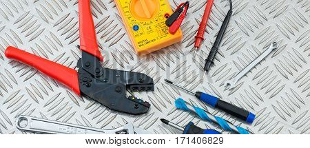 Electrician's Tools And Equipment On Steel Checker Plate