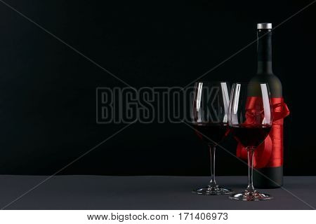 Wine bottle and two wineglasses on a dark background. Love card concept with copy space Valentine's day theme