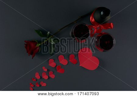 Wine bottle and two wineglasses with red hearts and rose flower on a dark background. Love card concept Valentine's day theme. Shot from above