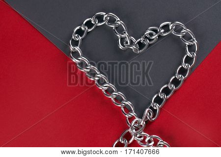 Chain shaped as heart on gray and red paper. Love card concept Valentine's day theme