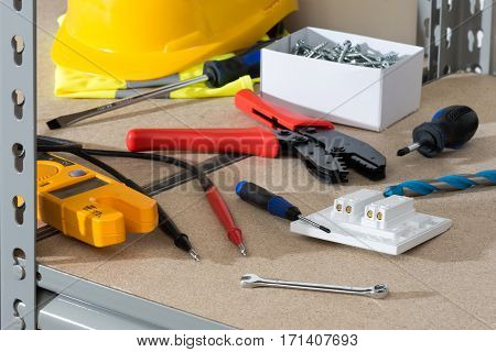 Electrician's Tools And Supplies On Cork-covered Shelving
