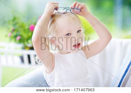 Portrait Of Beautiful Little Girl Wearing Glasses At Home